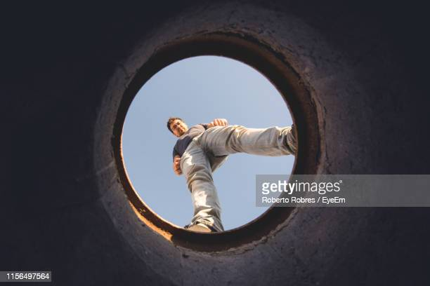 directly below shot of man seen through hole against sky - directly below stock pictures, royalty-free photos & images