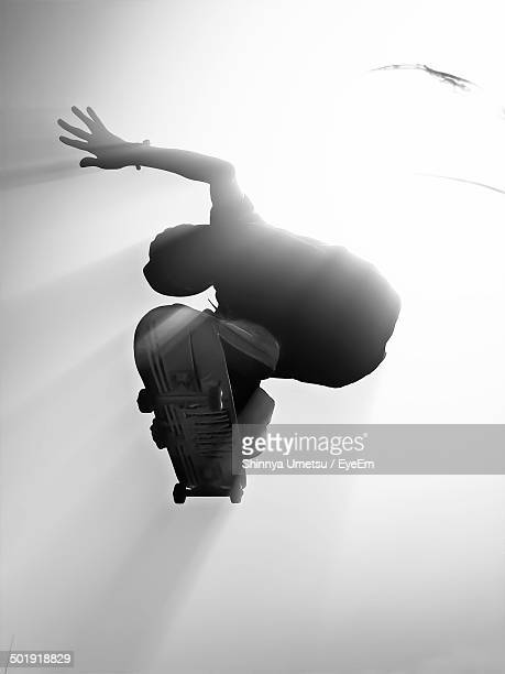 Directly below shot of man skateboarding against clear sky