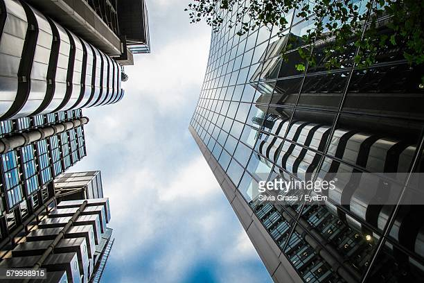 Directly Below Shot Of Modern Buildings Against Cloudy Sky In City