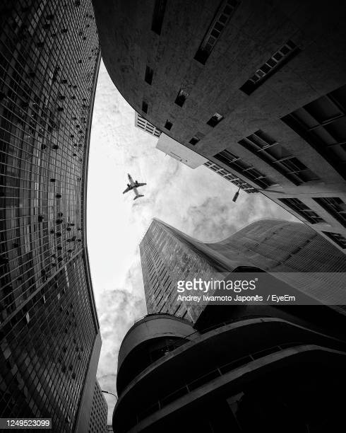 directly below shot of modern buildings against sky - japonês stock pictures, royalty-free photos & images