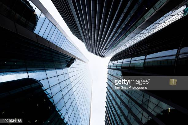 directly below shot of modern office skyscraper in the city of london's financial district. - real estate stock pictures, royalty-free photos & images