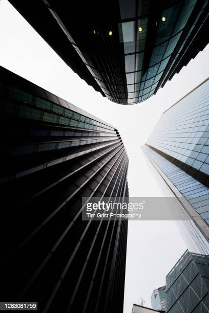 directly below shot of modern skyscrapers in the city of london - risk stock pictures, royalty-free photos & images
