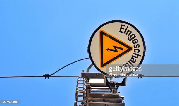 Directly Below Shot Of Sign Board On Power Line Against Clear Blue Sky