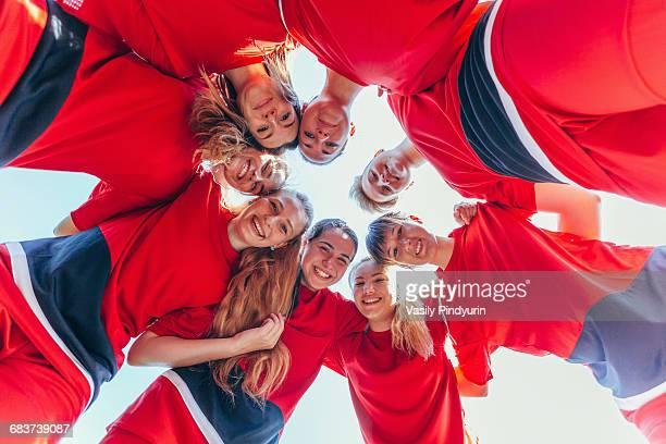 directly below shot of soccer players huddling against clear sky - teamsport stockfoto's en -beelden