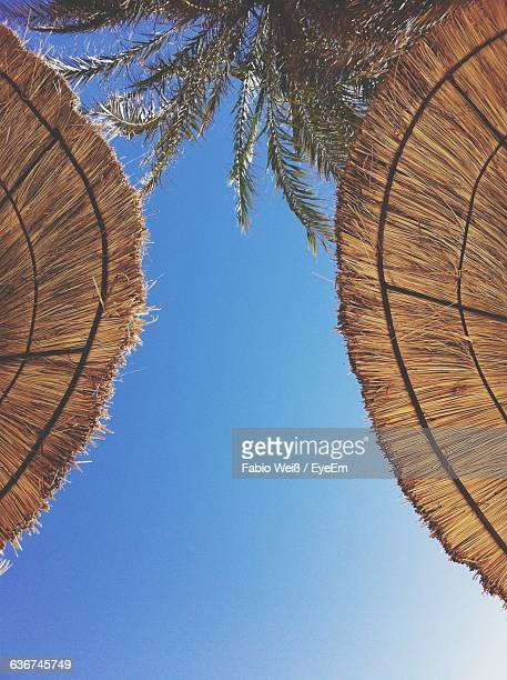 directly below shot of sunshades against blue sky - weiß stock pictures, royalty-free photos & images
