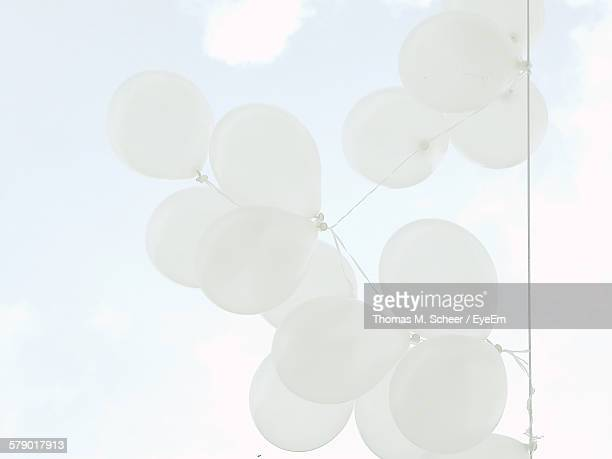 Directly Below Shot Of White Balloons Hanging From String Against Sky