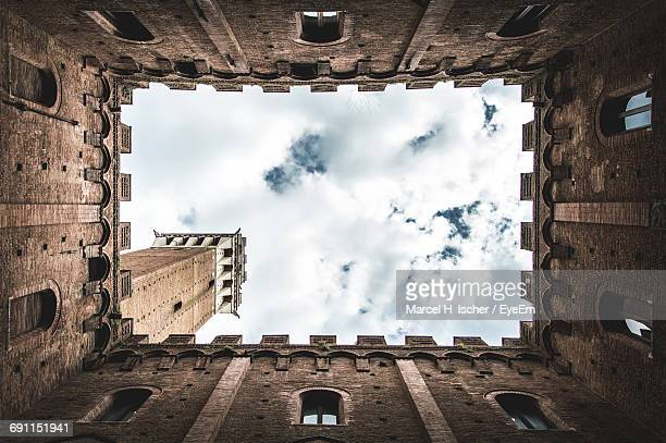 directly below shot torre del mangia against sky - campo stock photos and pictures