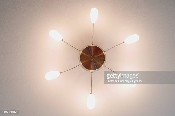 Directly Below View Of Illuminated Light Fixture On Ceiling
