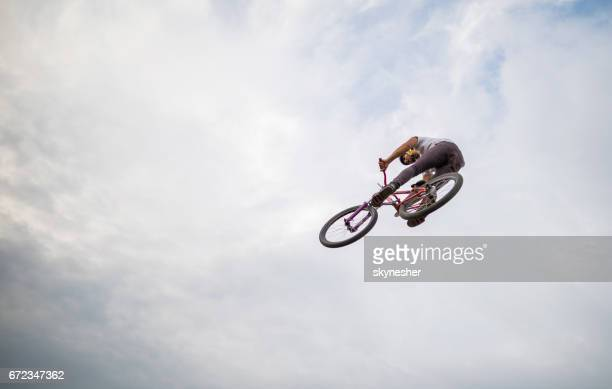 Directly below view of man on mountain bicycle against sky.