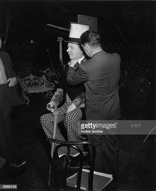 Director A Edward Sutherland adjusts comic actor W C Fields into the desired pose on the set of the film 'Poppy'