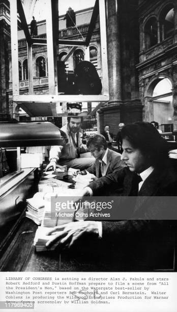 Director Alan J Pakula speaking to actors Robert Redford and Dustin Hoffman on the sets of the film 'All the President's Men' 1976
