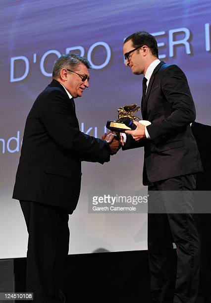"Director Aleksandr Sokurov of ""Faust"" accepts the Golden Lion for Best Film from jury member Darren Aronofsky during the Closing Ceremony during the..."