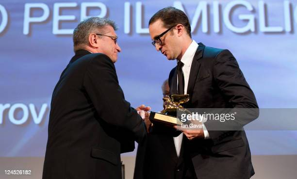 "Director Aleksandr Sokurov of ""Faust"" accepts the Golden Lion for Best Film from Jury President Darren Aronofsky during the Closing Ceremony during..."