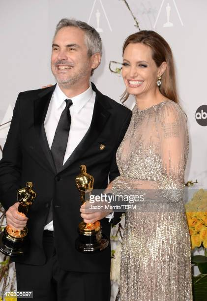 Director Alfonso Cuarón winner of Best Achievement in Directing and actress Angelina Jolie poses in the press room during the Oscars at Loews...
