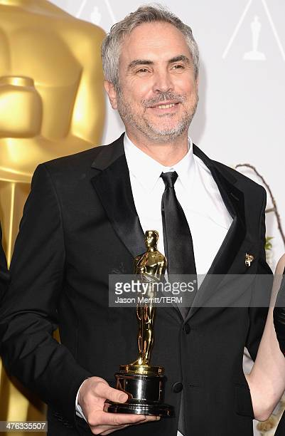 Director Alfonso Cuaron winner of Best Achievement in Editing poses in the press room during the Oscars at Loews Hollywood Hotel on March 2 2014 in...