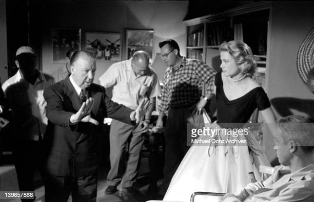 Director Alfred Hitchcock plans a shot with his crew and actress Grace Kelly on the set of the Paramount Pictures movie 'Rear Window' in November...