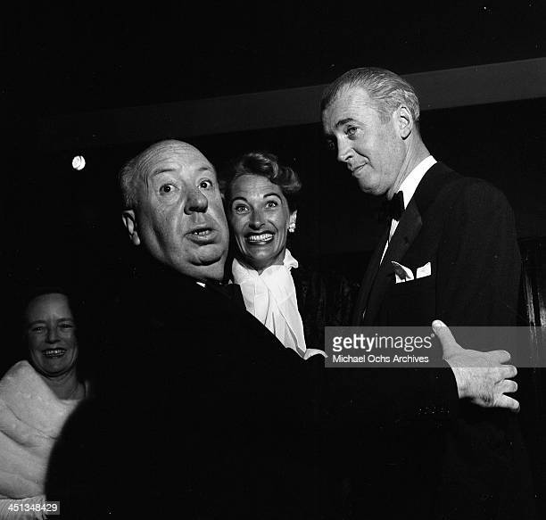 Director Alfred Hitchcock talk to actor Jimmy Stewart and his wife Gloria Hatrick McLean as they attend the premier of The Man Who Knew Too Much in...