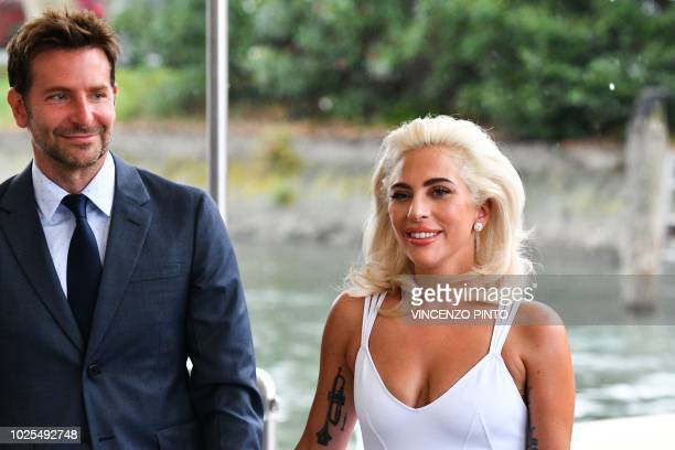 Director and actor Bradley Cooper and singer and actress Lady Gaga arrive by boat under the rain at the Excelsior Hotel on August 31 2018 during the...