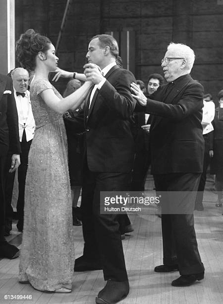 Director and actor Charlie Chaplin directing his daughter Geraldine Chaplin and actor Marlon Brando in a dance sequence during the filming of A...