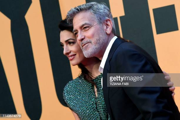 US director and actor George Clooney and his wife LebaneseBritish humanrights lawyer Amal Clooney pose on the red carpet upon their arrival for the...