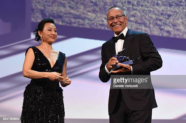 Director Andrey Konchalovskiy poses onstage with Jury member Joan Chen with the Silver Lion for Best Director he received for his movie 'The...
