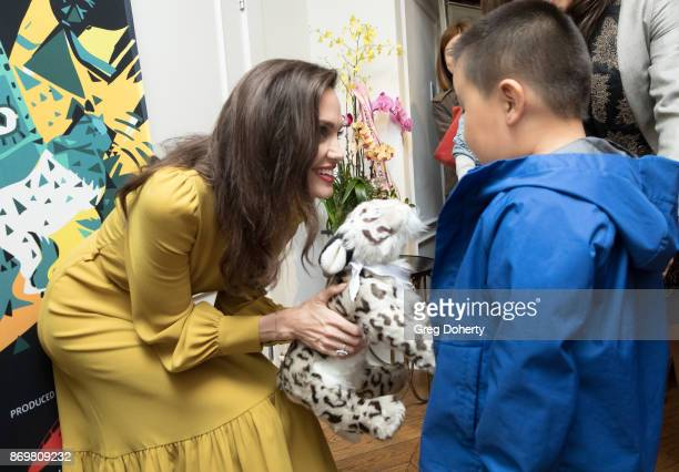 Director Angelina Jolie accepts a gift of a Snow Leopard from Aidan Sherniyazova as she attends a reception before a screening of the movie 'First...