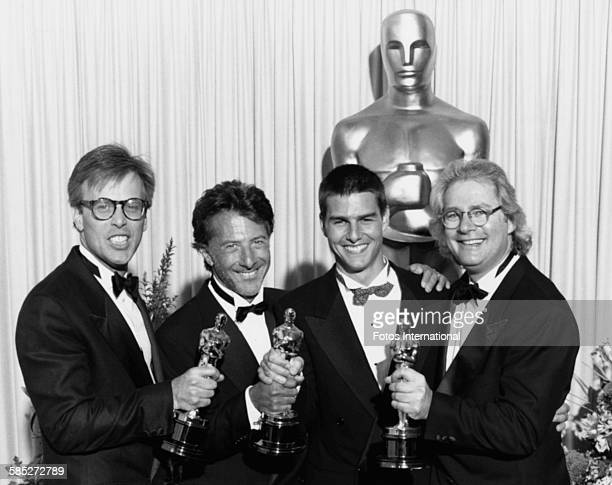 Director Barry Levinson producer Mark Johnson and actor Dustin Hoffman holding their Oscar statuettes for the film 'Rain Man' with costar Tom Cruise...