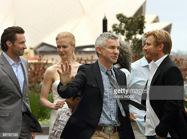 Director Baz Luhrmann waves in front of actress Nicole Kidman actor Hugh Jackman and actor David Wenham during a photo shoot following a press...