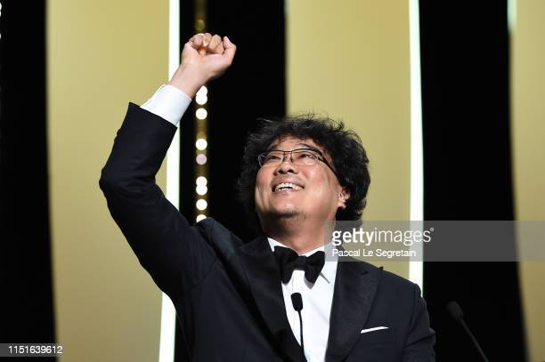 "Director Bong Joon-Ho reacts after winning the Palme d'Or award for ""Parasite"" on stage during the Closing Ceremony of the 72nd annual Cannes Film..."