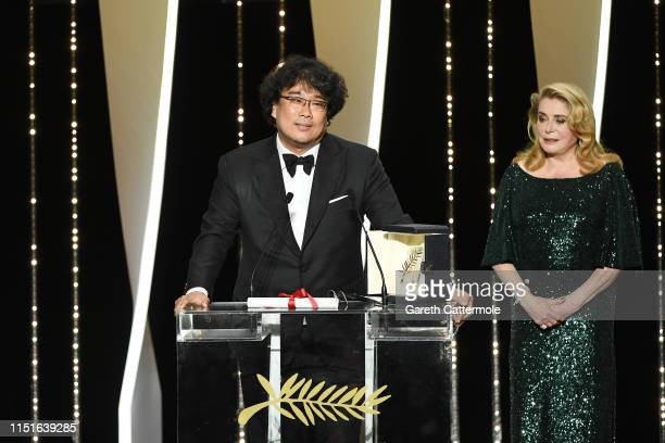 Director Bong JoonHo receives the Palme d'Or award for Parasite from Catherine Deneuve on stage during the Closing Ceremony of the 72nd annual Cannes...