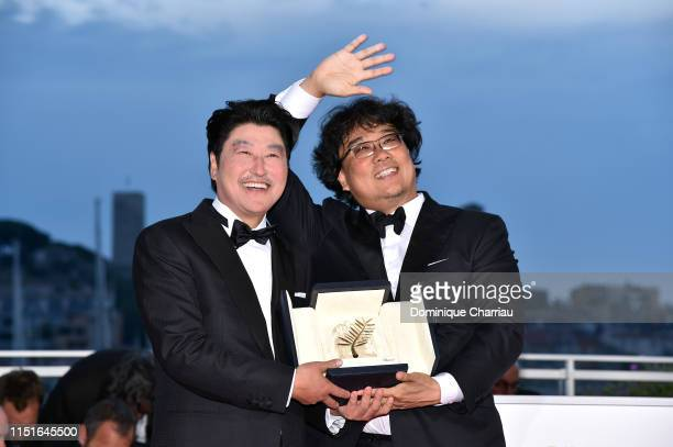 Director Bong JoonHo winner of the Palme d'Or award for his film Parasite poses with Actor KangHo Song at the winner photocall during the 72nd annual...