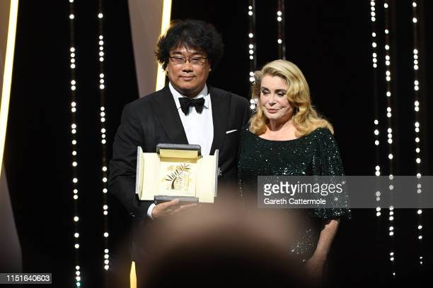 Director Bong JoonHo with the Palme d'Or award for Parasite and Catherine Deneuve on stage during the Closing Ceremony of the 72nd annual Cannes Film...