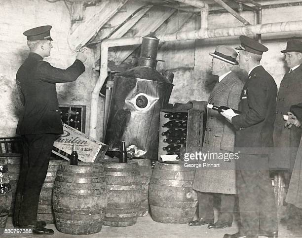 Director Butler inspects a battle of illegal beverage in the cellar of the 61st and Thompson Street station house in Philadelphia he is accompanied...