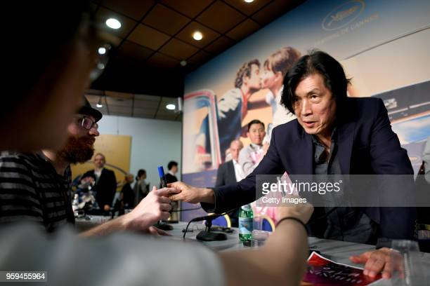 Director Changdong Lee signs autographs as he attends 'Burning' Press Conference during the 71st annual Cannes Film Festival at Palais des Festivals...