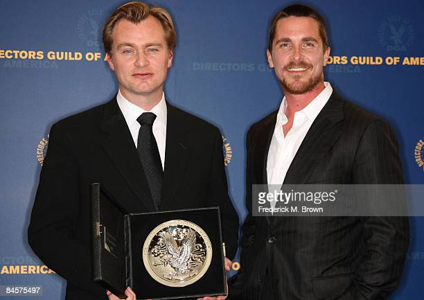 Director Christopher Nolan poses with his Feature Film Nomination plaque for The Dark Night with presenter Christian Bale in the press room during...
