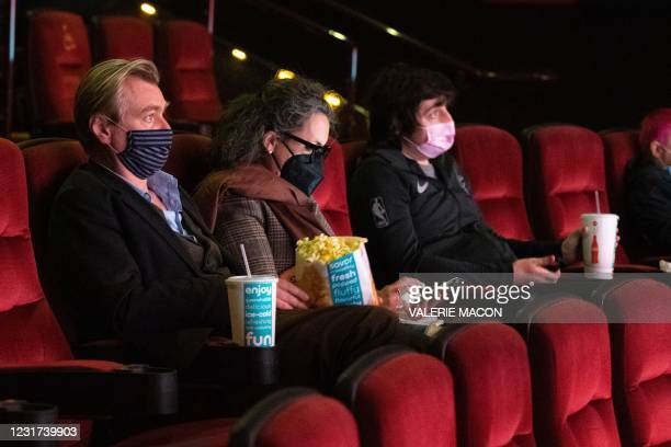 "Director Christopher Nolan sits in the AMC Burbank theatre to watch ""Judas and the Black Messiah"" on reopening day in Burbank, California, March 15,..."