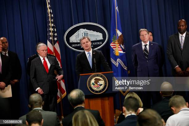 Director Christopher Wray accompanied by officials including Attorney General Jeff Sessions speaks at a press conference about the apprehension of a...