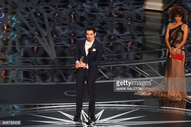 US director Damien Chazelle delivers a speech on stage next to US actress Halle Berry after he won the Best Director award for 'La La Land'at the...