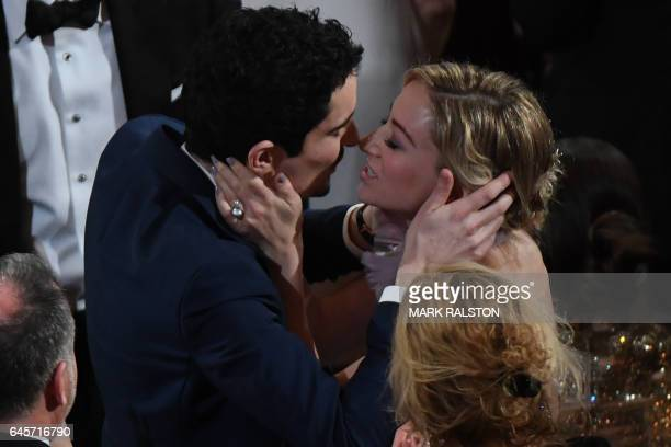 TOPSHOT US director Damien Chazelle kisses his partner Olivia Hamilton after he won the Best Director award for 'La La Land'at the 89th Oscars on...