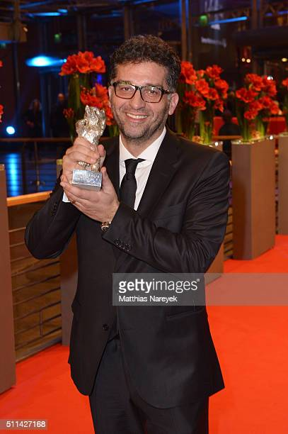 Director Danis Tanovic winner of the Silver Bear Grand Jury Prize for his movie 'Mort à Sarajevo' poses with his award after the closing ceremony of...