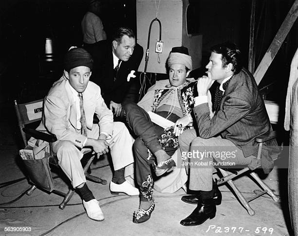 Director David Butler leaning down to talk to actors Bing Crosby Bob Hope and Joel McCrea on the set of the film 'Road to Morocco' for Paramount...