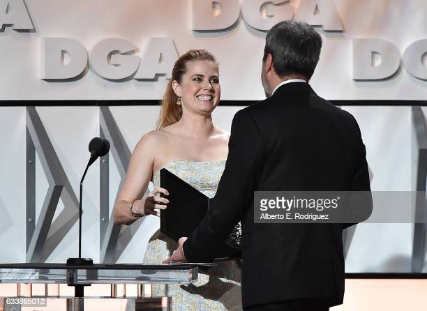 """Director Denis Villeneuve accepts the Feature Film Nomination Plaque for """"Arrival"""" from actress Amy Adams onstage during the 69th Annual Directors..."""
