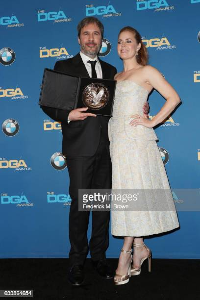 "Director Denis Villeneuve , recipient of the Feature Film Nomination Plaque for ""Arrival,"" poses with actress Amy Adams in the press room during the..."