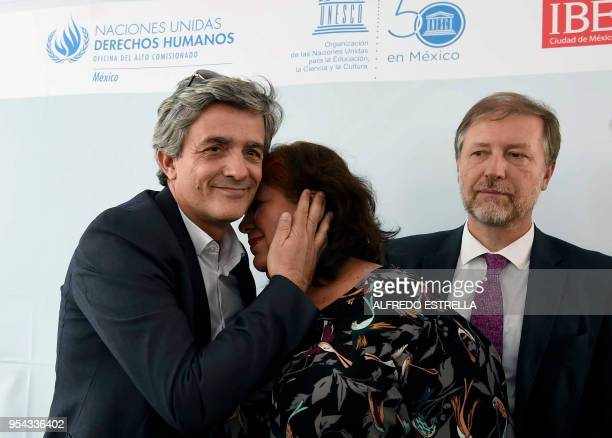 AFP Director for Latin America Pierre Ausseill greets Griselda Triana the widow of slain Mexican journalist Javier Valdez during the award ceremony...