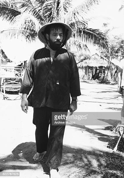 Director Francis Ford Coppola walking outdoors wearing a straw hat on location making the movie 'Apocalypse Now' circa 1979
