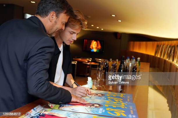 Director Francois Ozon and actor Félix Lefebvre sign the movie poster before the premiere of their film Ete 85 on July 07 2020 in Lille France