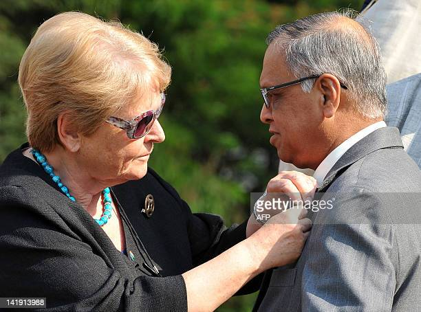 Director General Emiritus of WHO and former minister of Norway Gro Harlem Brundtland puts a badge on Chief Mentor of Infosys Technologies NR Narayana...