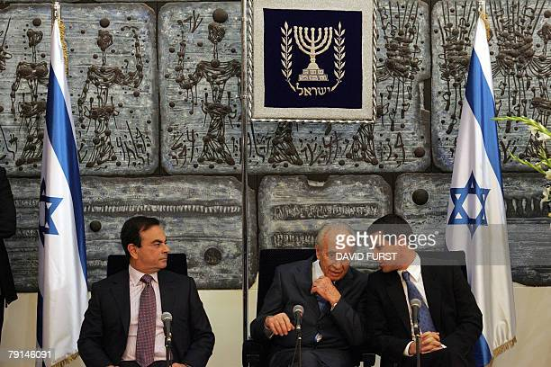 Director General of Better Project Shai Agassi whispers to Israeli President Shimon Peres as President of French automaker RenaultNissan Carlos Ghosn...