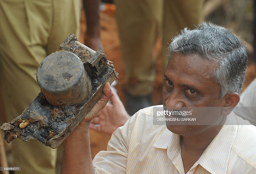 A Director General of Civil Aviation (DGCA) official holds up an aircraft part which officials claim is the 'black box' of the doomed Air India Express flight 812, discovered at the crash site in Mangalore on May 25, 2010. Investigators recovered May 25 the 'black box' digital flight recorder that holds crucial clues to the crash of an Air India Express plane in southern India that killed 158 people. The discovery followed an intense three-day search that began hours after the Boeing 737-800, flying from Dubai to the city of Mangalore, overshot the runway May 22, plunged into a gorge and burst into flames. AFP PHOTO/Dibyangshu Sarkar