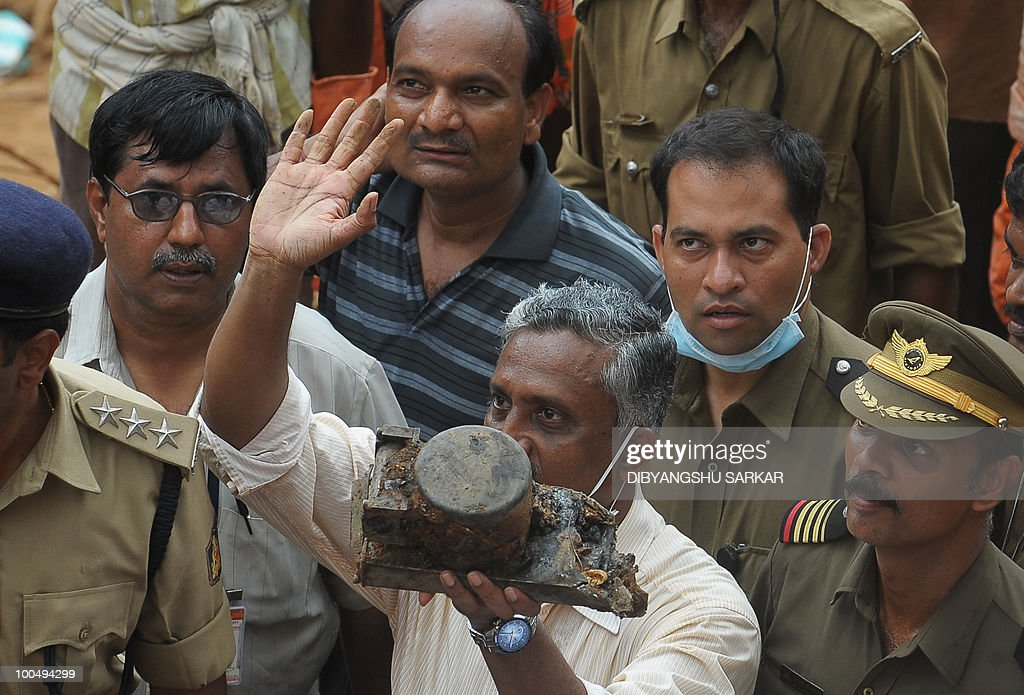 A Director General of Civil Aviation (DGCA) official (C) holds up an aircraft part which officials claim is the 'black box' of the doomed Air India Express flight 812, discovered at the crash site in Mangalore on May 25, 2010. Investigators recovered May 25 the 'black box' digital flight recorder that holds crucial clues to the crash of an Air India Express plane in southern India that killed 158 people. The discovery followed an intense three-day search that began hours after the Boeing 737-800, flying from Dubai to the city of Mangalore, overshot the runway May 22, plunged into a gorge and burst into flames. AFP PHOTO/Dibyangshu Sarkar